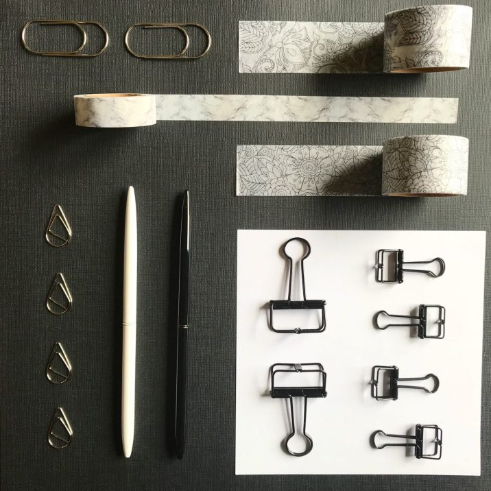 Black Stationery Flat Lay with Pens, Paperclips, Binderclips and Washi Tape