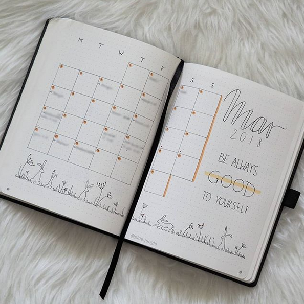 A hand drawn calendar for the month of March is shown across two Bullet Journal pages. There are rabbits, grass and flower drawn horiztonally along the bottom of the two pages.